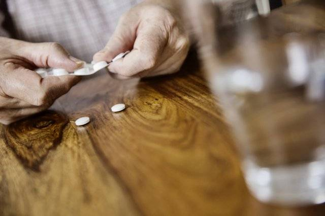 Белые таблетки и стакан воды