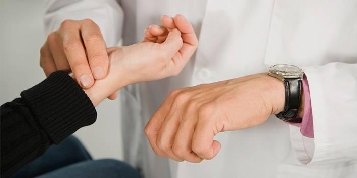 Доктор измеряет частоту пульса у пациента
